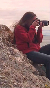 Alex, in her natural habitat, atop a rock with something watery in her viewfinder. Photo by Michael Stillwater.